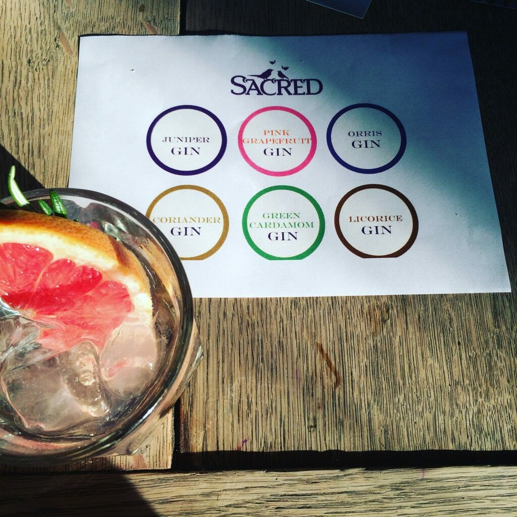 Sacred G&T next to the tasting mat of 6 different Sacred gins
