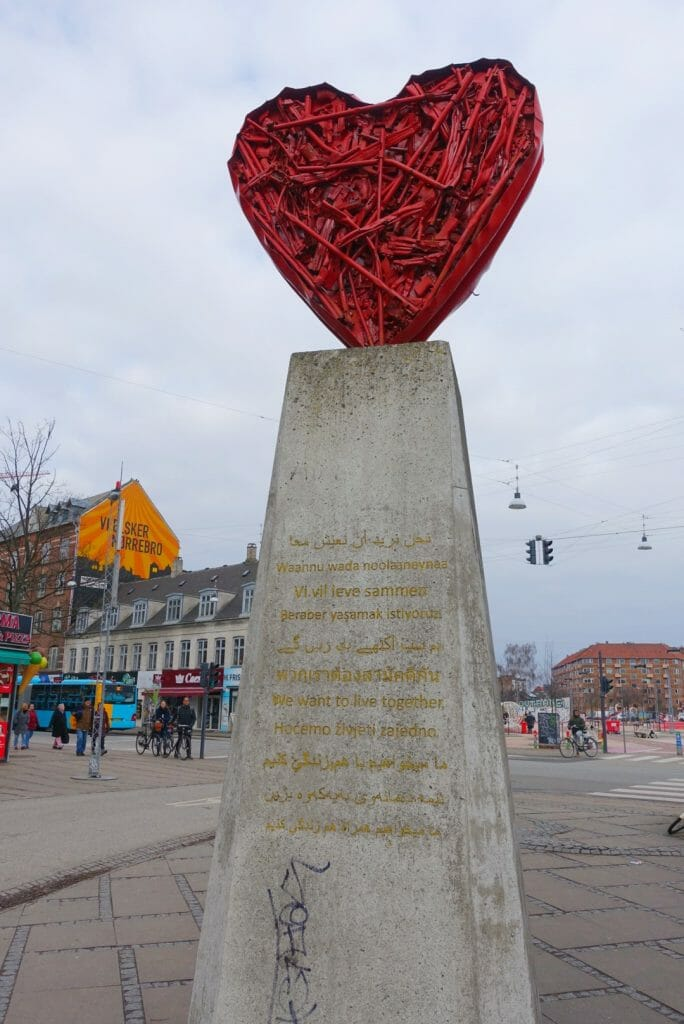 Statue of a red heart with 'We want to live together' in all the languages of the local people on it