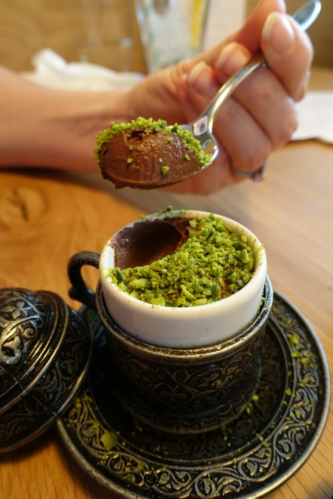 Spoon of pistachio topped chocolate mousse