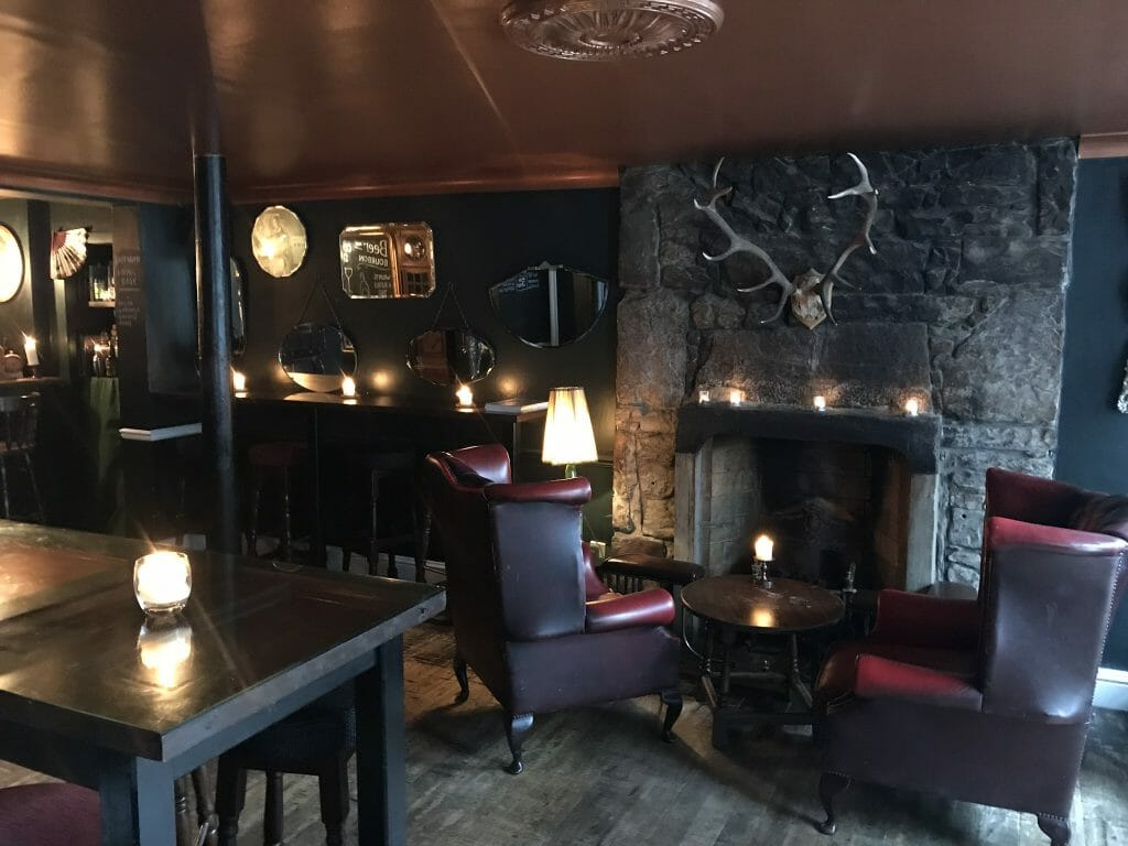 The cosy interior of The Last Word bar with armchairs and stag antlers