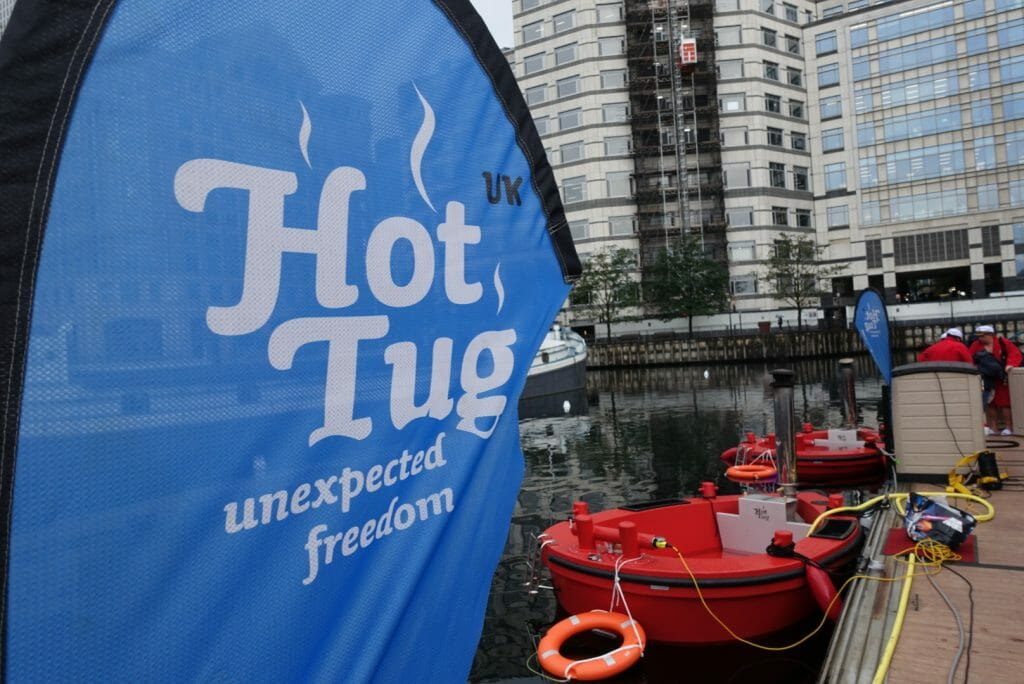 The HotTug sign and HotTug boat in the water behind it