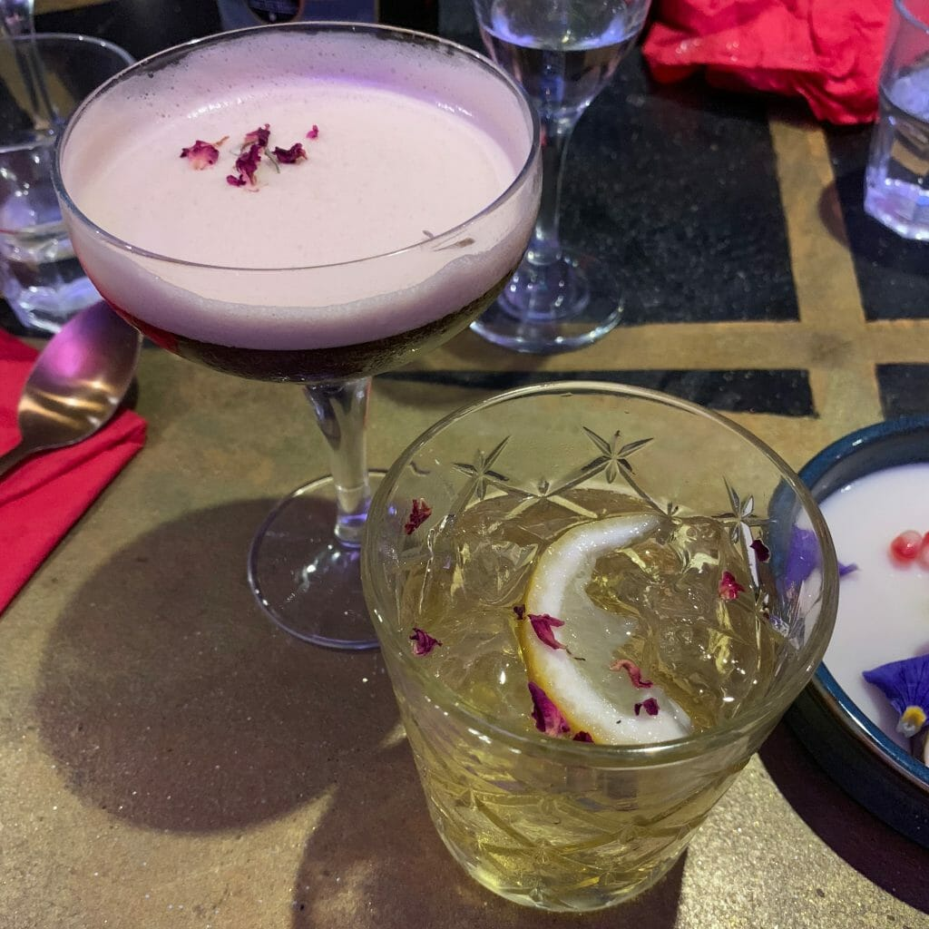 Espresso martini and white negroni, both decorated with rose petals