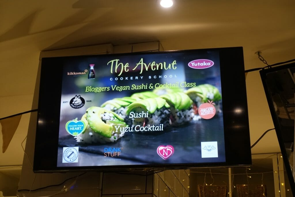 TV screen showing the bloggers vegan sushi and cocktail class info