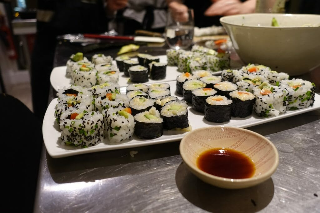 Plates full of sushi and a bowl of soy sauce