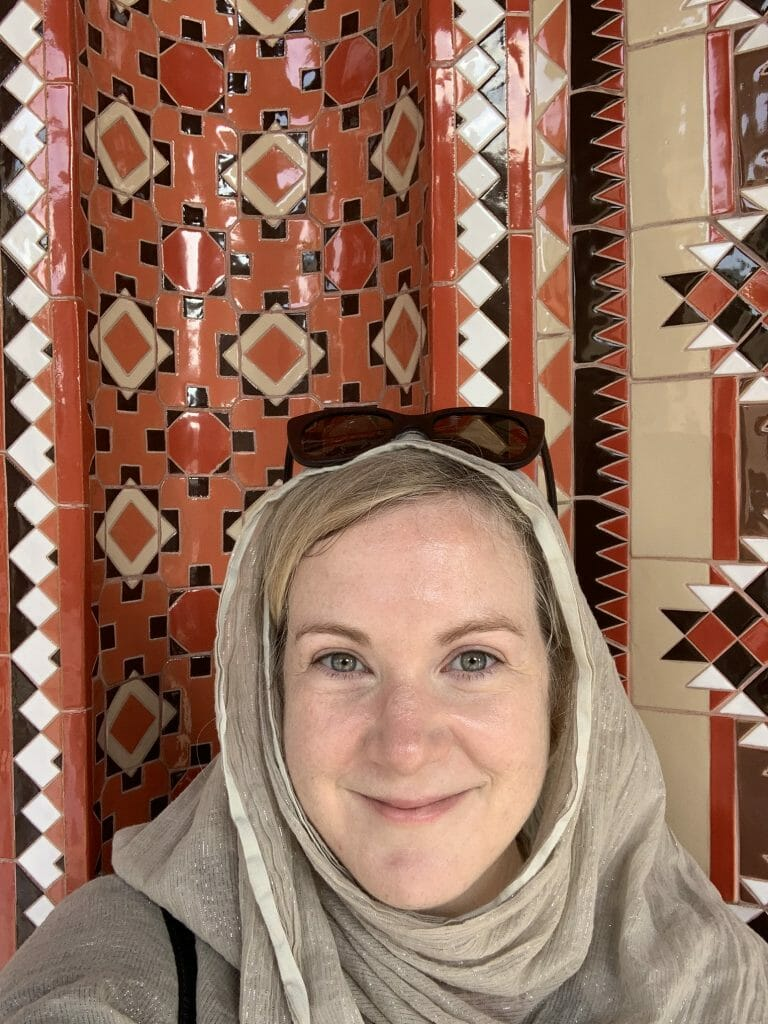 Katie taking a selfie in headscarf in front of geometric patterned tiles