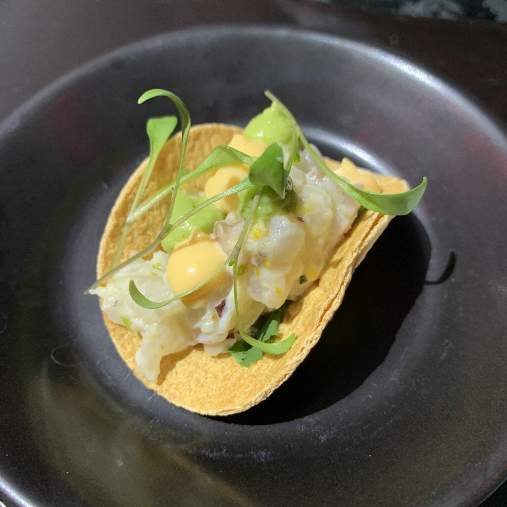 Small taco with seabream ceviche inside and garnished with microherbs