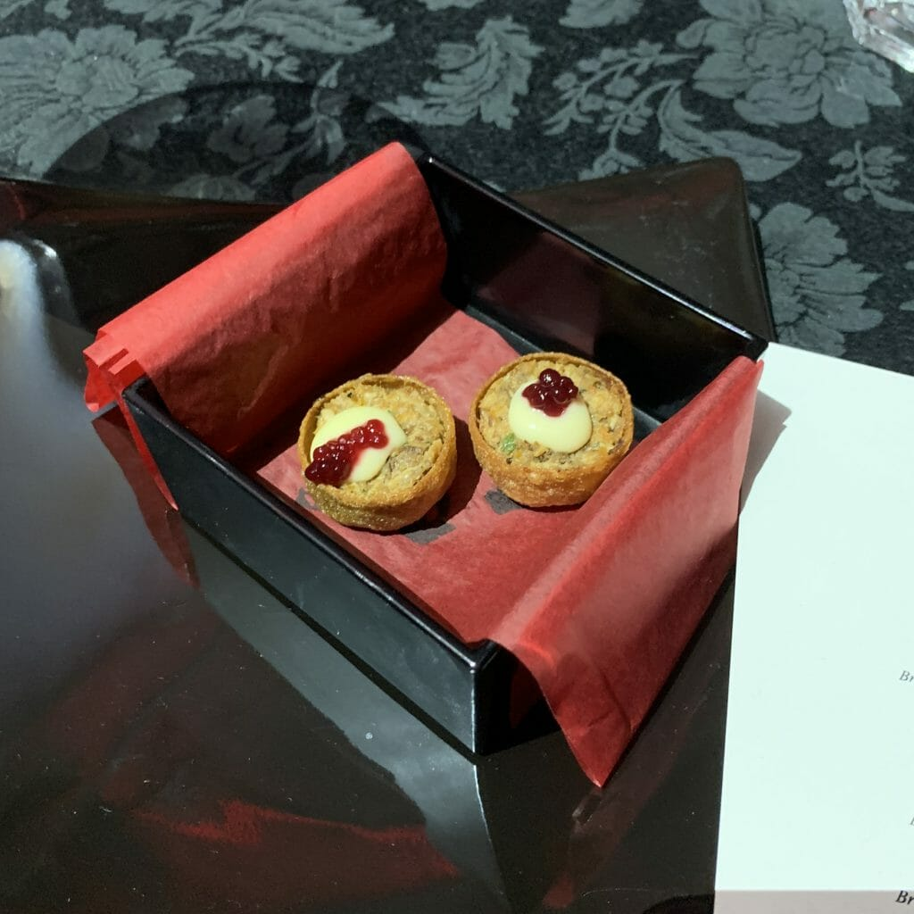 Two game tartlets in a black lacquer box with red tissue paper