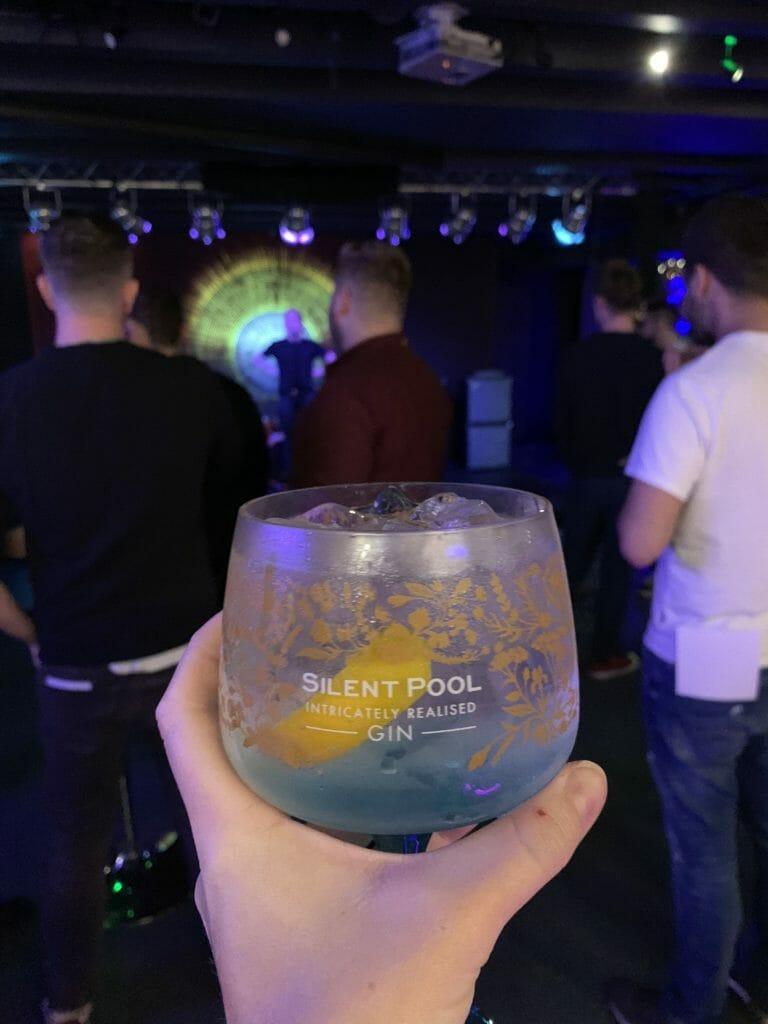 Blue Silent Pool G&T glass with decorative motives and lemon peel garnish