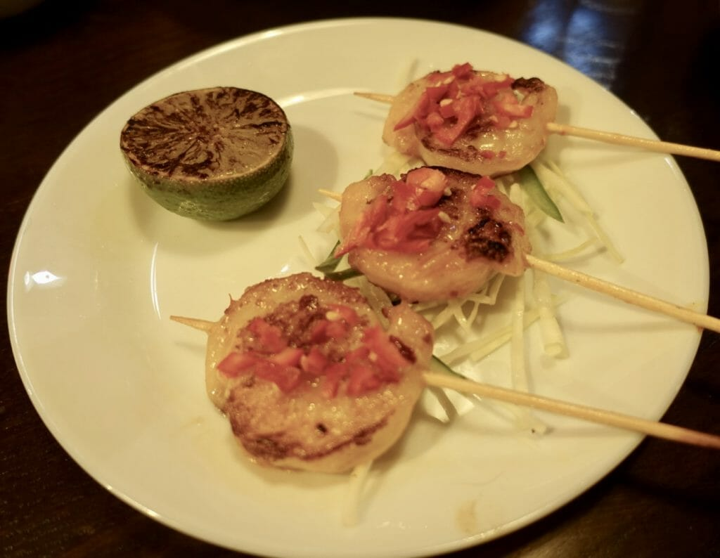 Prawns served like lollipops on sticks with fresh chili on top