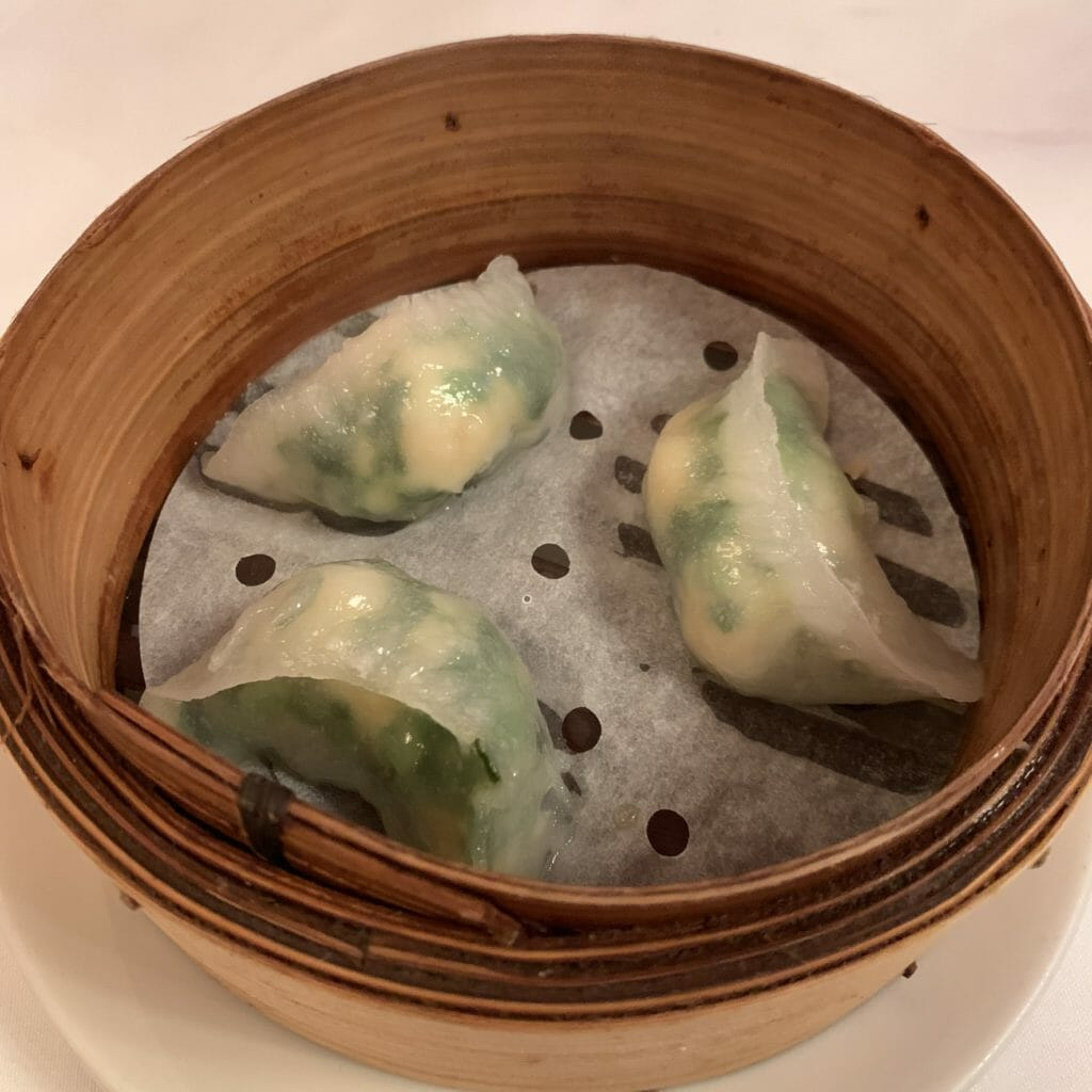 Three prawn and chive dumplings in a bamboo steamer