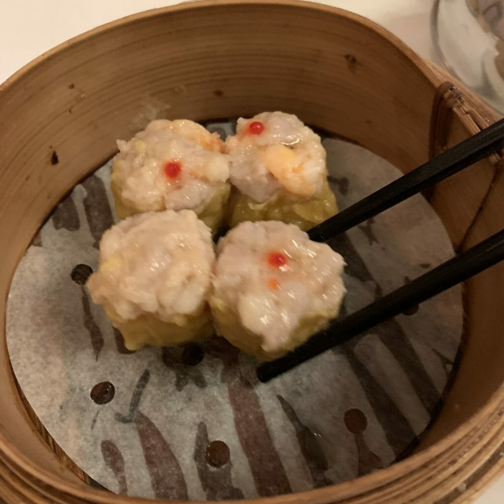 Siu Mai pork and prawn dumplings in the steamer with chopsticks