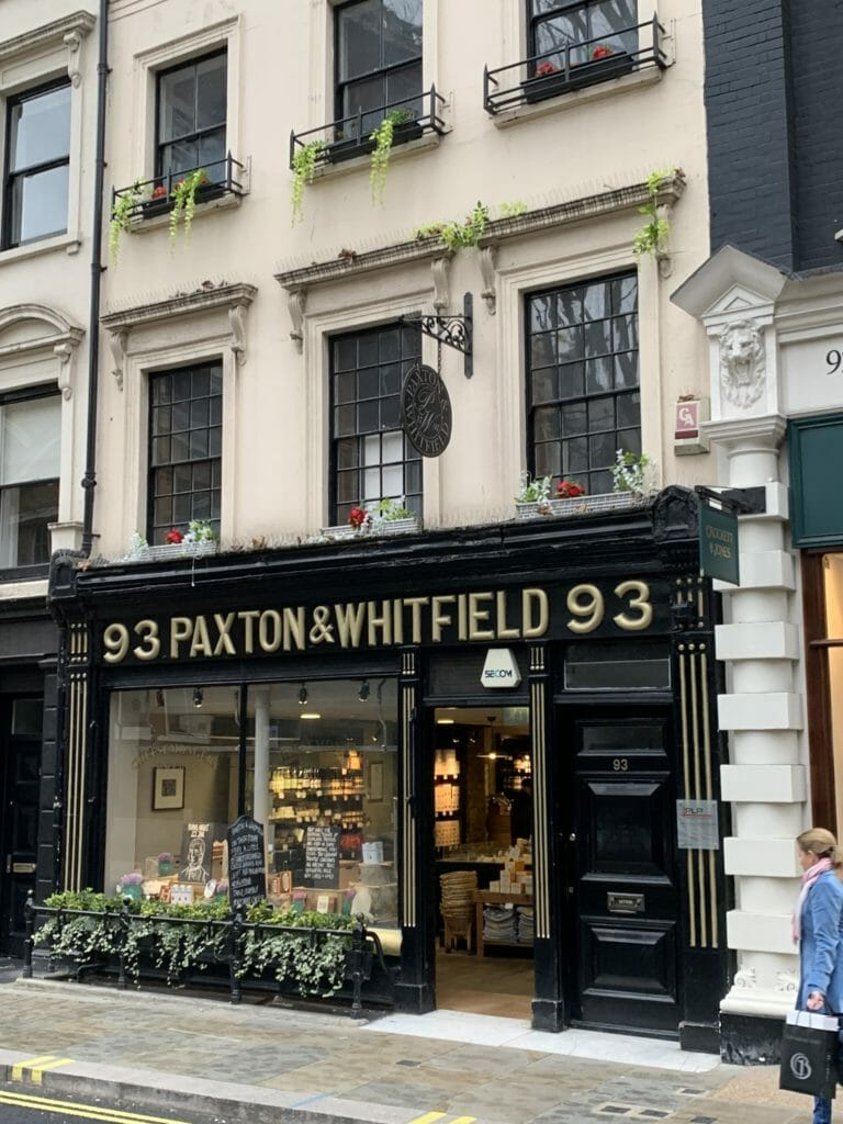 The exterior of Paxton and Whitfield with its black wood paneling and gilt lettering