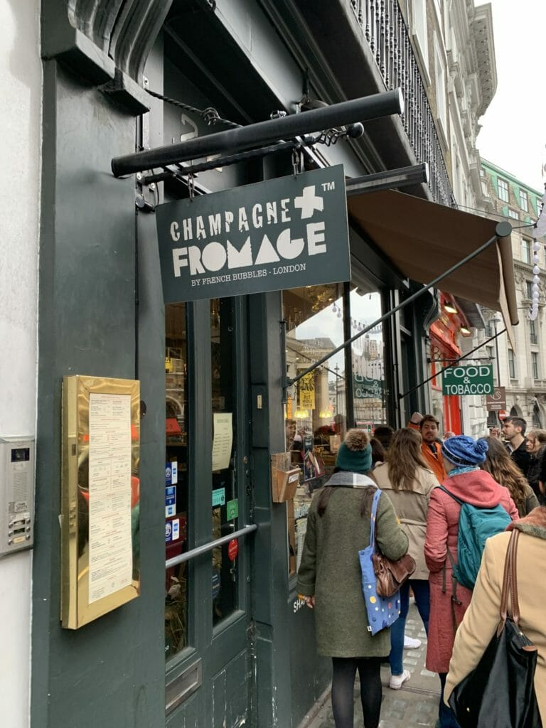 The sign and frontage of Champagne + Fromage