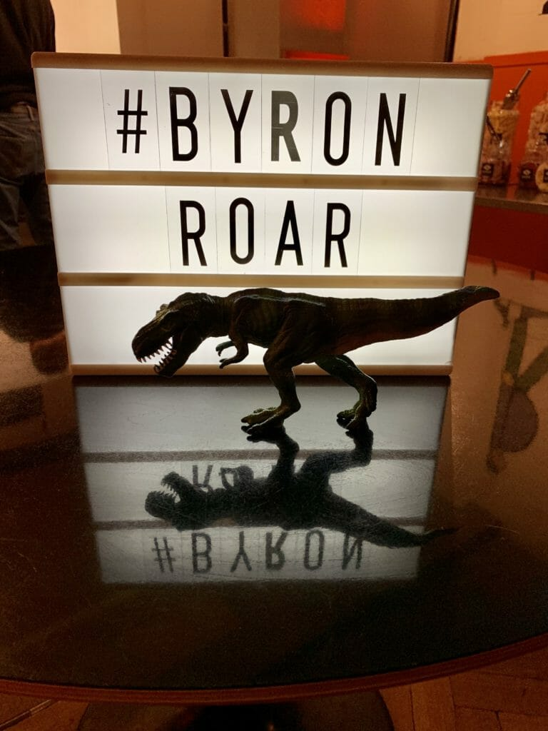 Katie's T-Rex toy stalking the B-Rex in front of the #ByronRoar sign