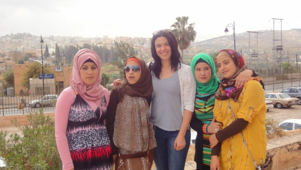 Katie's friend Cat posing with local Jordanian school girls at Jerash