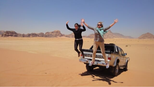 Katie and friend jumping off the truck in the desert near Wadi Rum - What to wear as a woman in Jordan