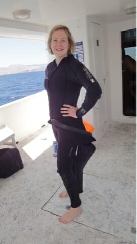 Katie posing on the boat in 1.5 wetsuits