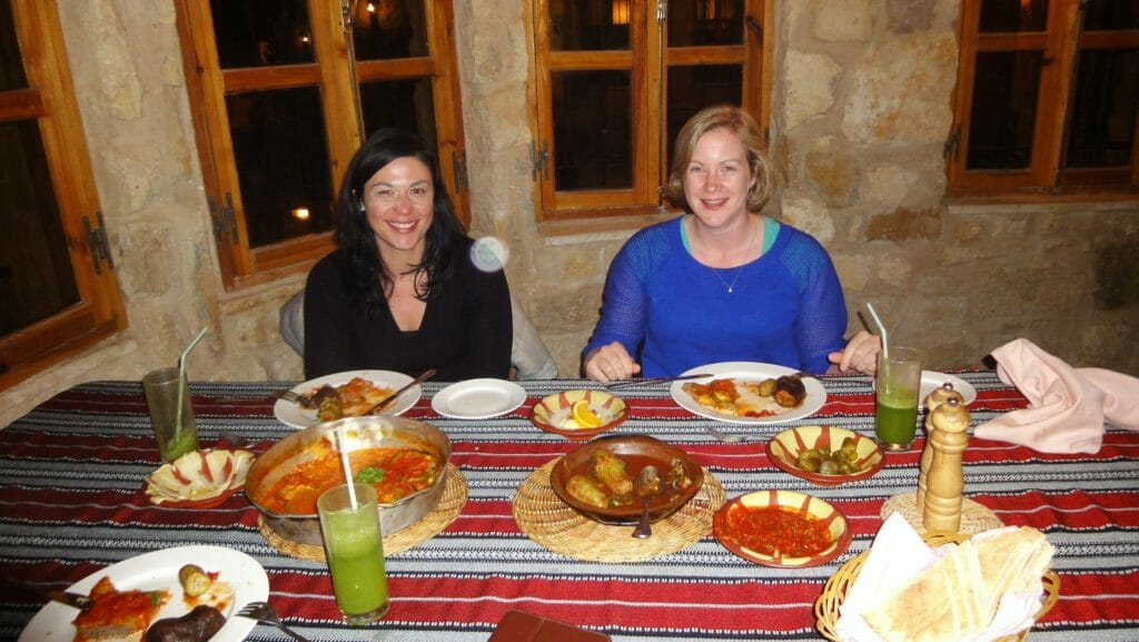 Katie and friend eating a traditional dinner wearing jumpers