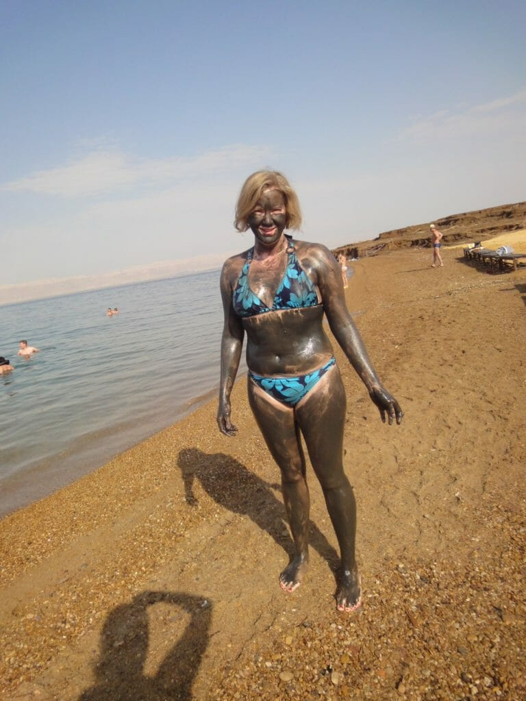 Katie in dark patterned bikini and full mud pack by the Dead Sea