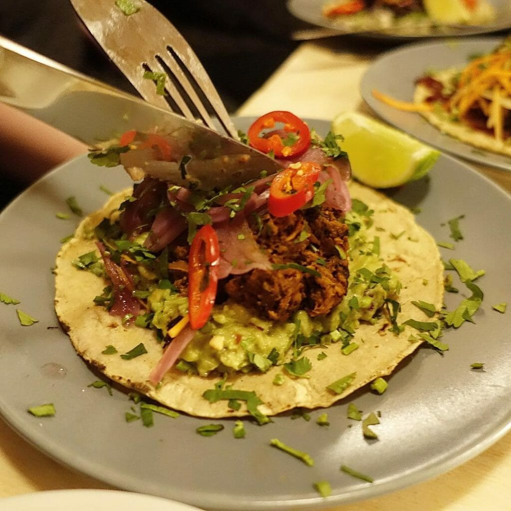 Knife and fork cutting into the pulled pork taco
