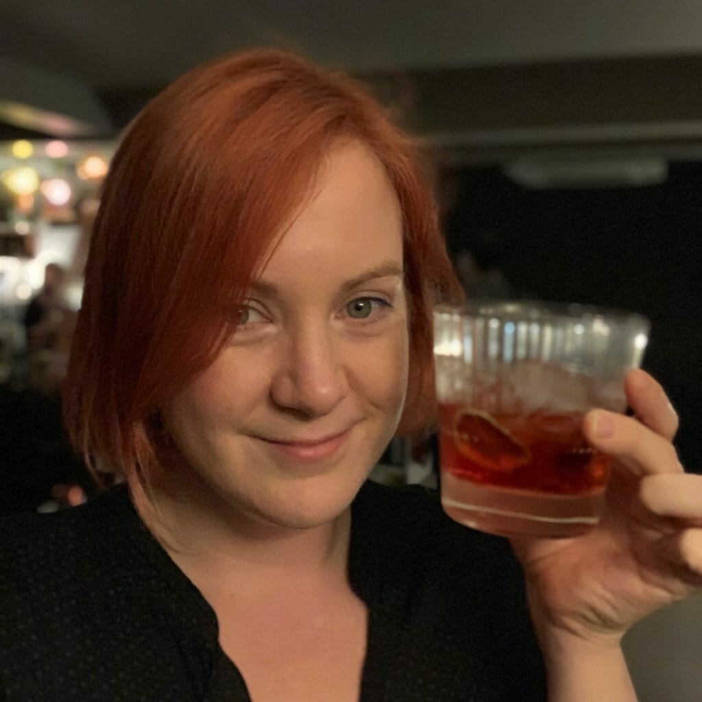 Katie with red hair matching the negroni in her hand