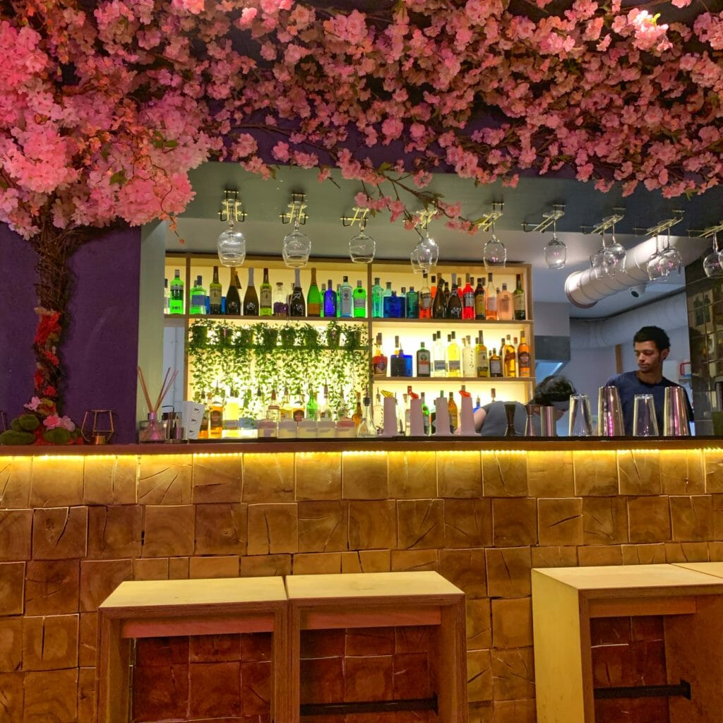 The bar area with a cascade of fake pink flowers growing over it