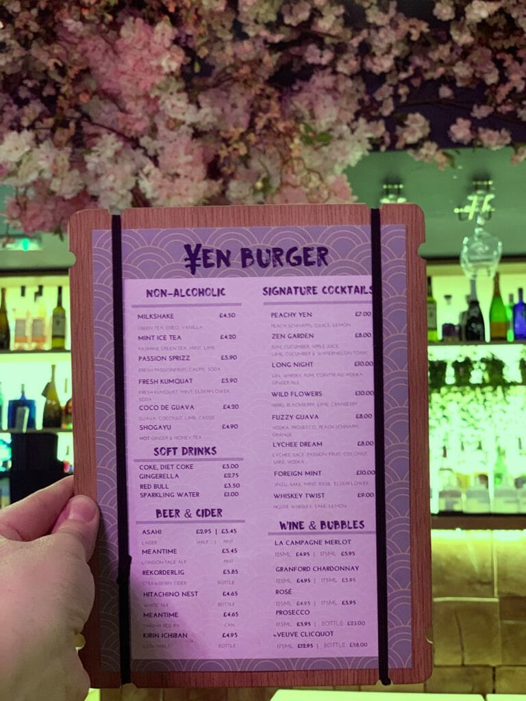 The Yen burger drinks menu being held up with the floral bar in the background