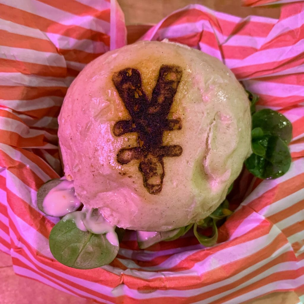 Overhead view of the burger showing the Japanese Yen currency symbol stamped on the bun