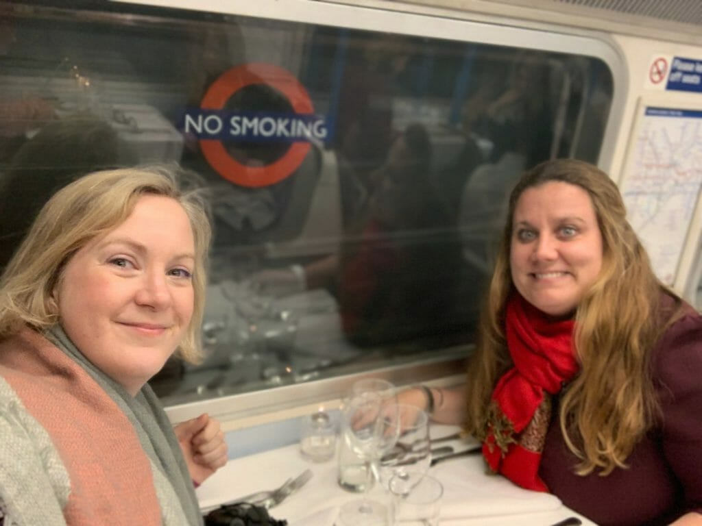 Katie and friend wearing scarfs at their table on the tube