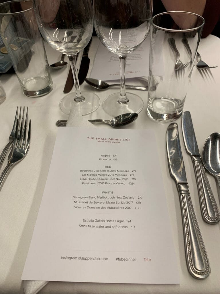 The drinks menu on the table with cutlery and glasses