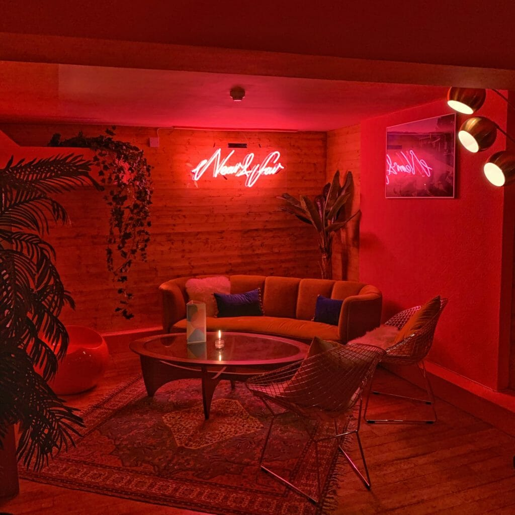 The neon sign lights up the sofa seating area with a pink glow in this private area