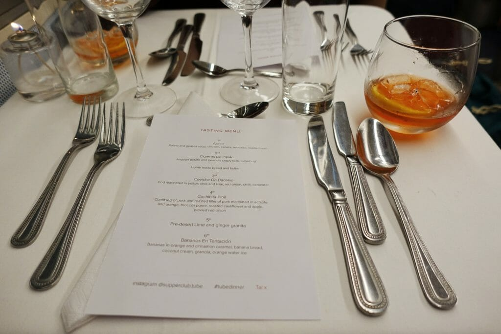 The menu for the evening on the table with cutlery and glasses