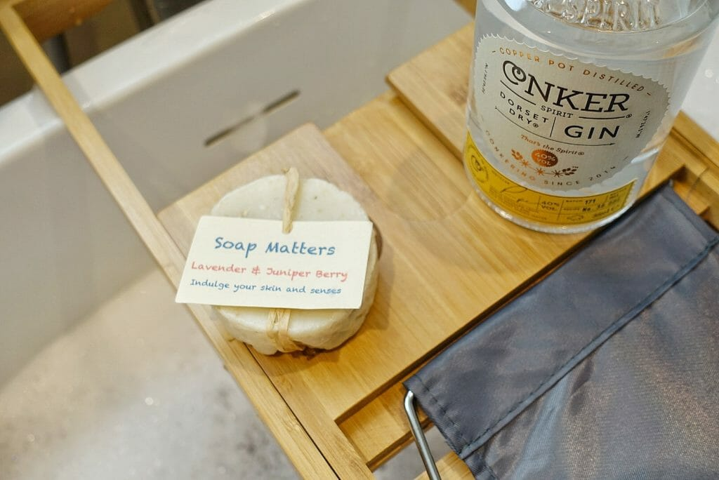 Conker gin bottle and lavender and juniper berry soap on the bath tray