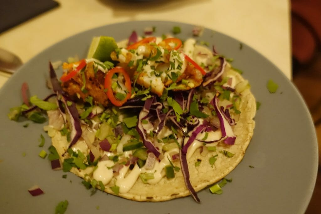Grilled fish taco served with lime mayo and finely sliced red cabbage
