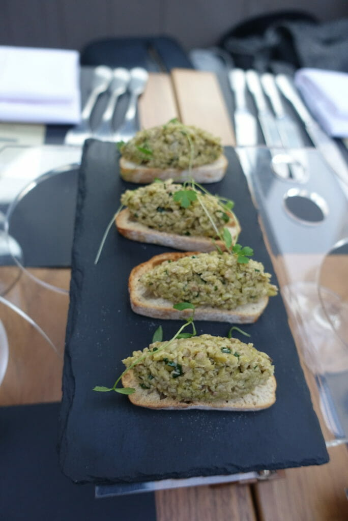 Green olive tapenade bruschetta served on a slate