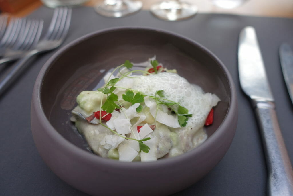 Grey bowl of mackerel ceviche with a coconut foam and avocado