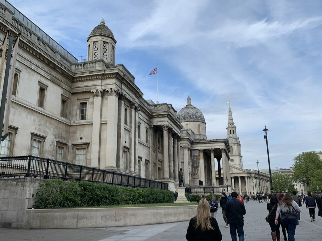 People walking past the front of the National Gallery towards the church
