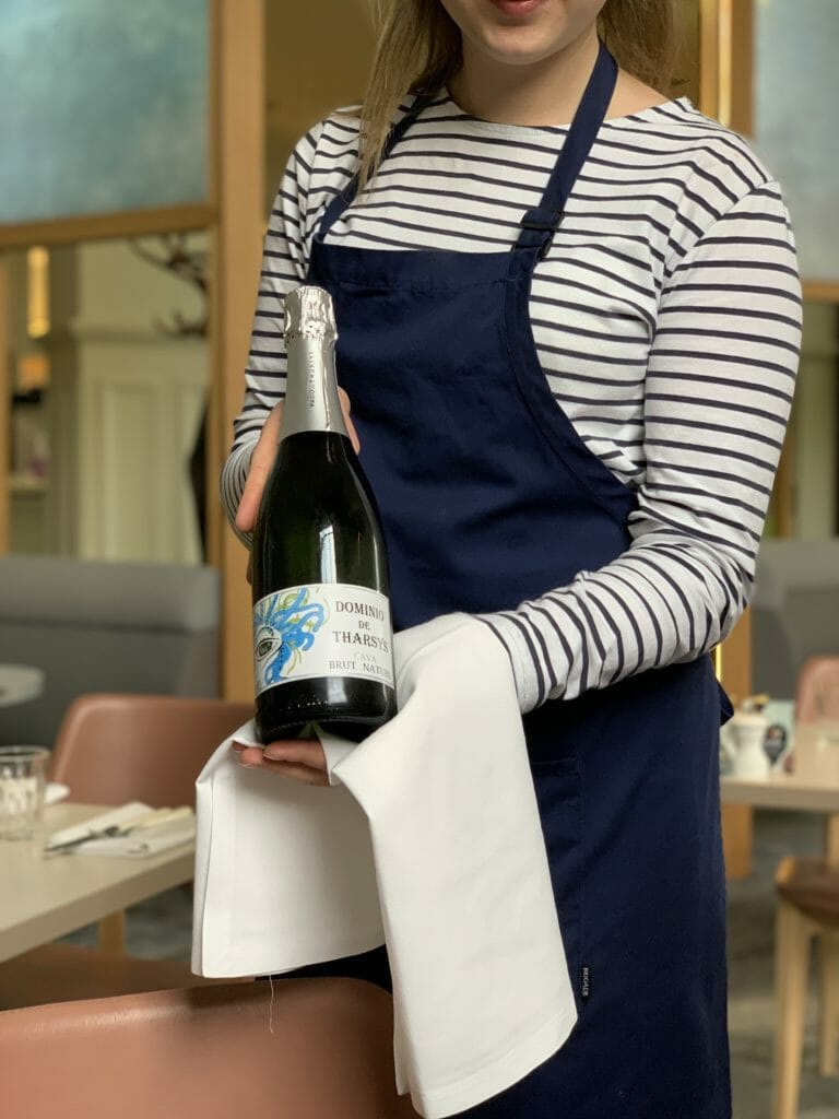 Bottle of cava being held by the waitress