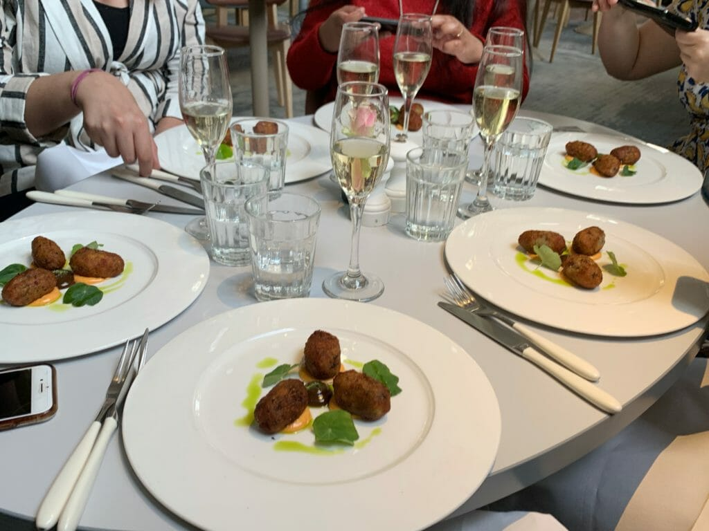Shot of the table with 6 plates of croquettes on it