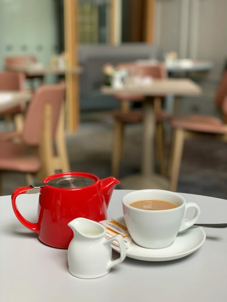 Red teapot with milk jug and tea cup