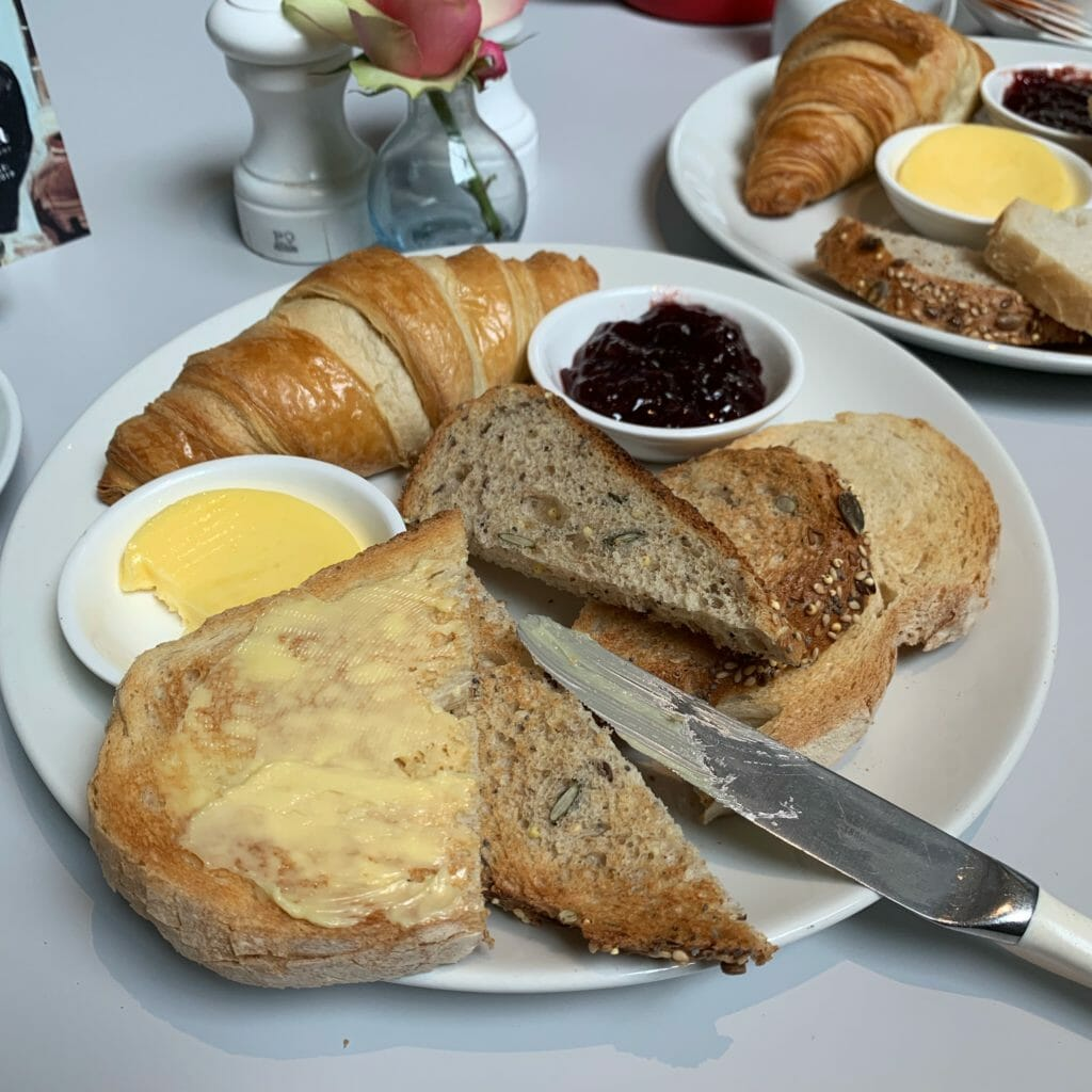 Plate of toast, crossiant with butter and jam