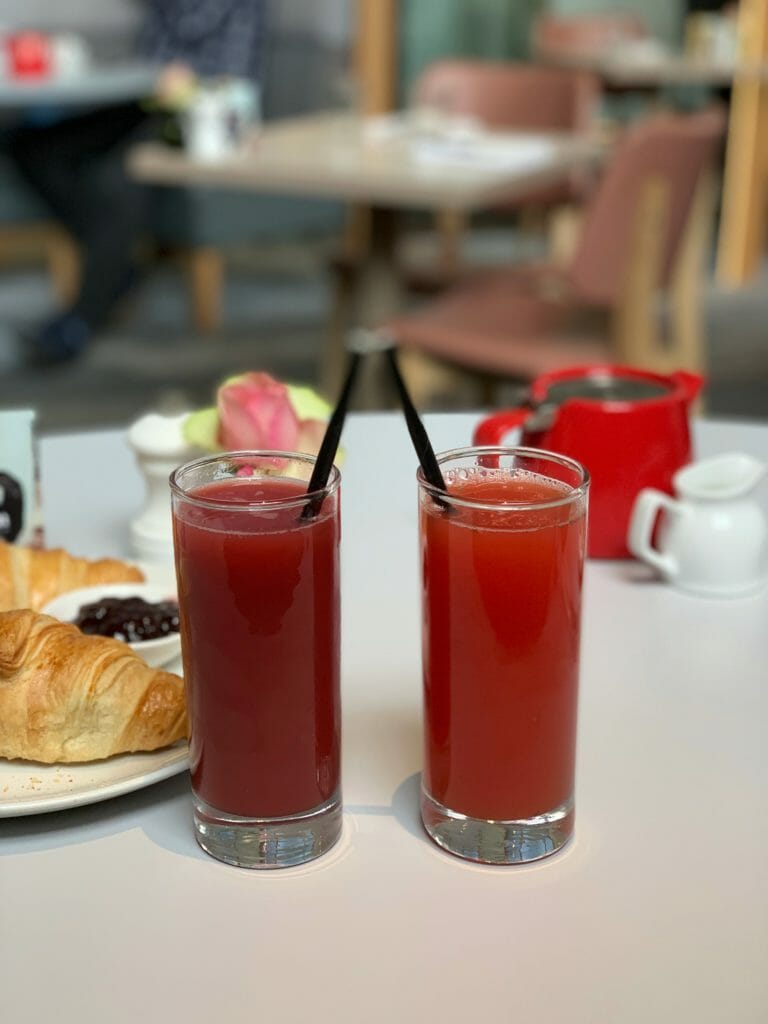 Two red juices with the red tea pot in the background