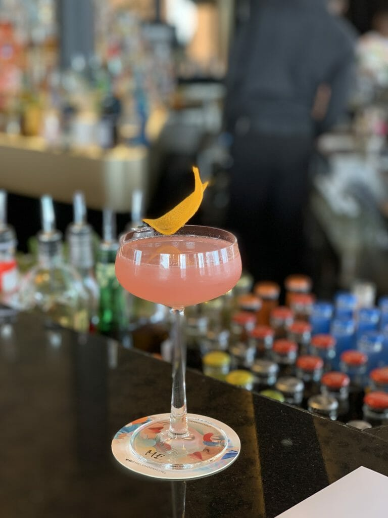 Coupe glass with pink cocktail garnished with orange peel