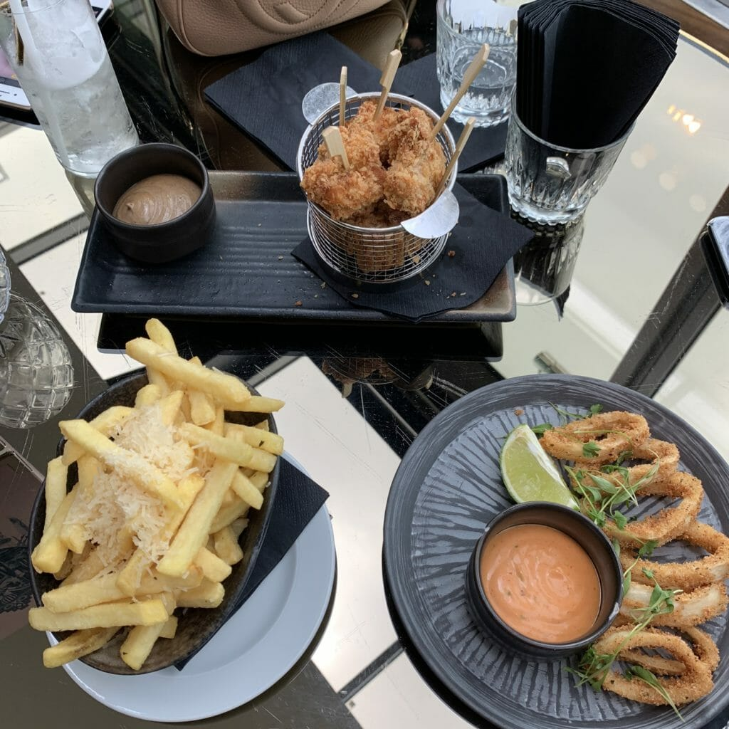 Fried chicken on sticks, sliced squid rings and chips with parmesan on top