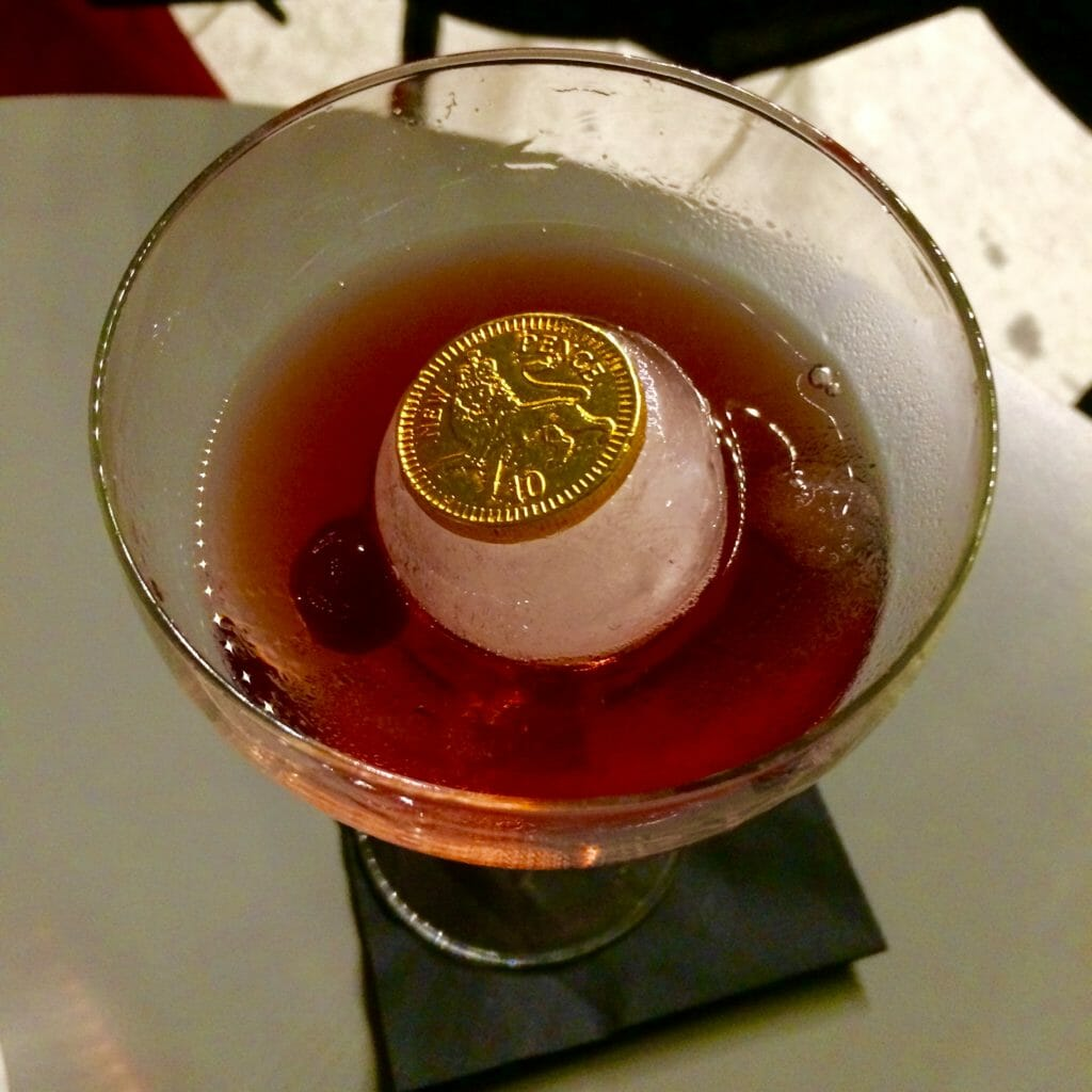 Chocolate coin embedded into the ice ball in the cocktail