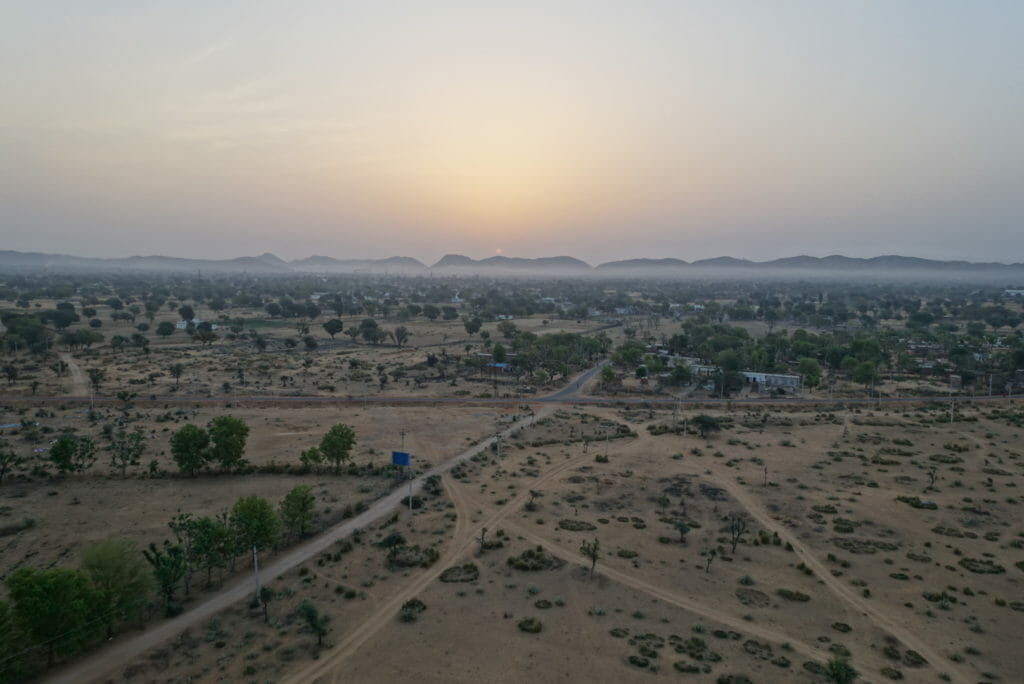 The sun rising over the distant Aravalli hills with countryside below