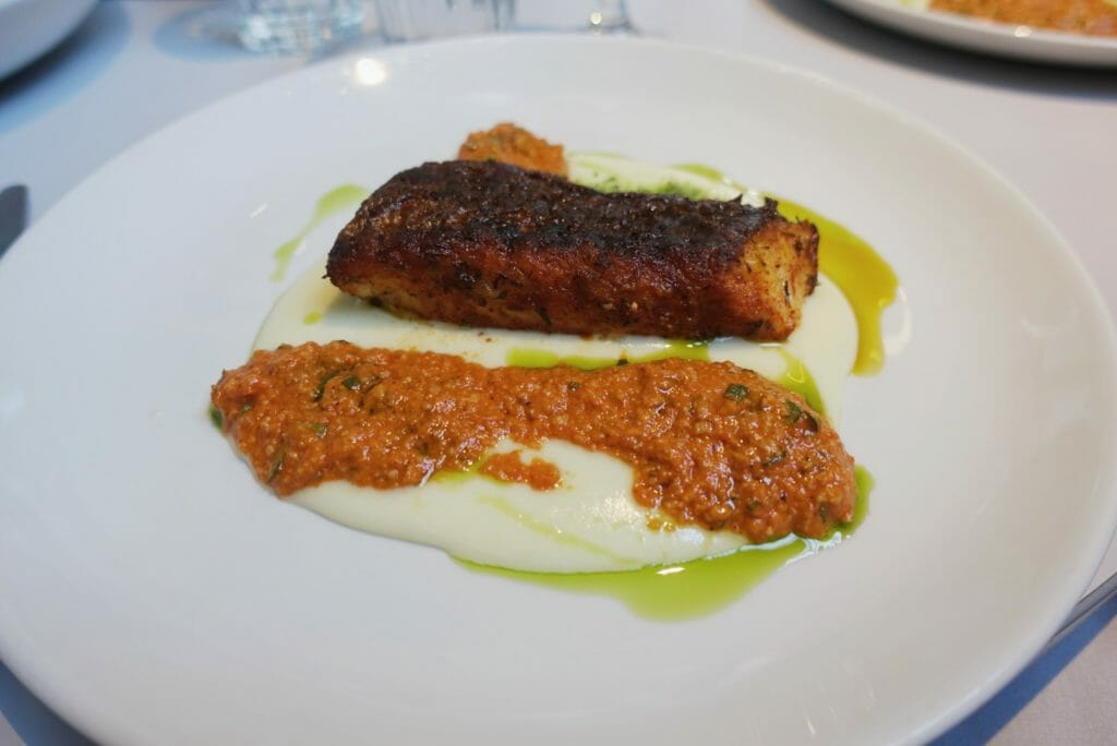 Hake on potato puree with a red romesco sauce & green oil