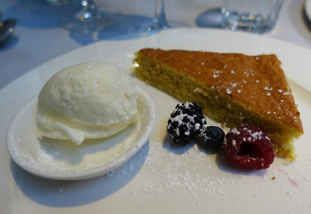 Slice of Tarta de Santiago with ice cream and berries