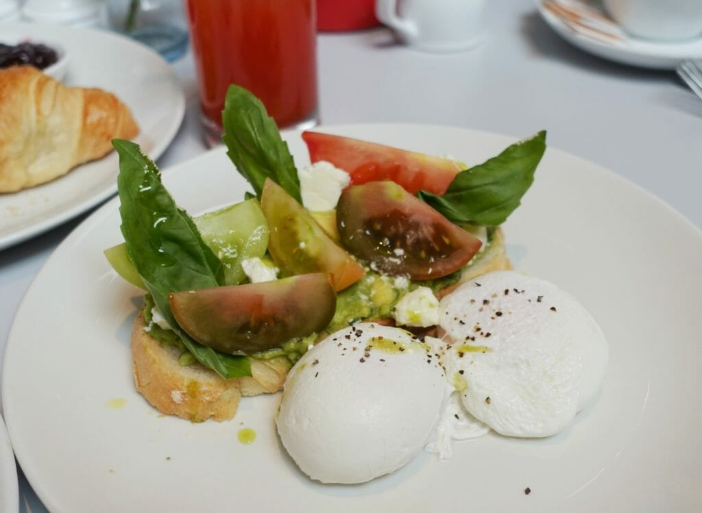 Avocado on toast with poached eggs, heritage tomatoes and fresh basil
