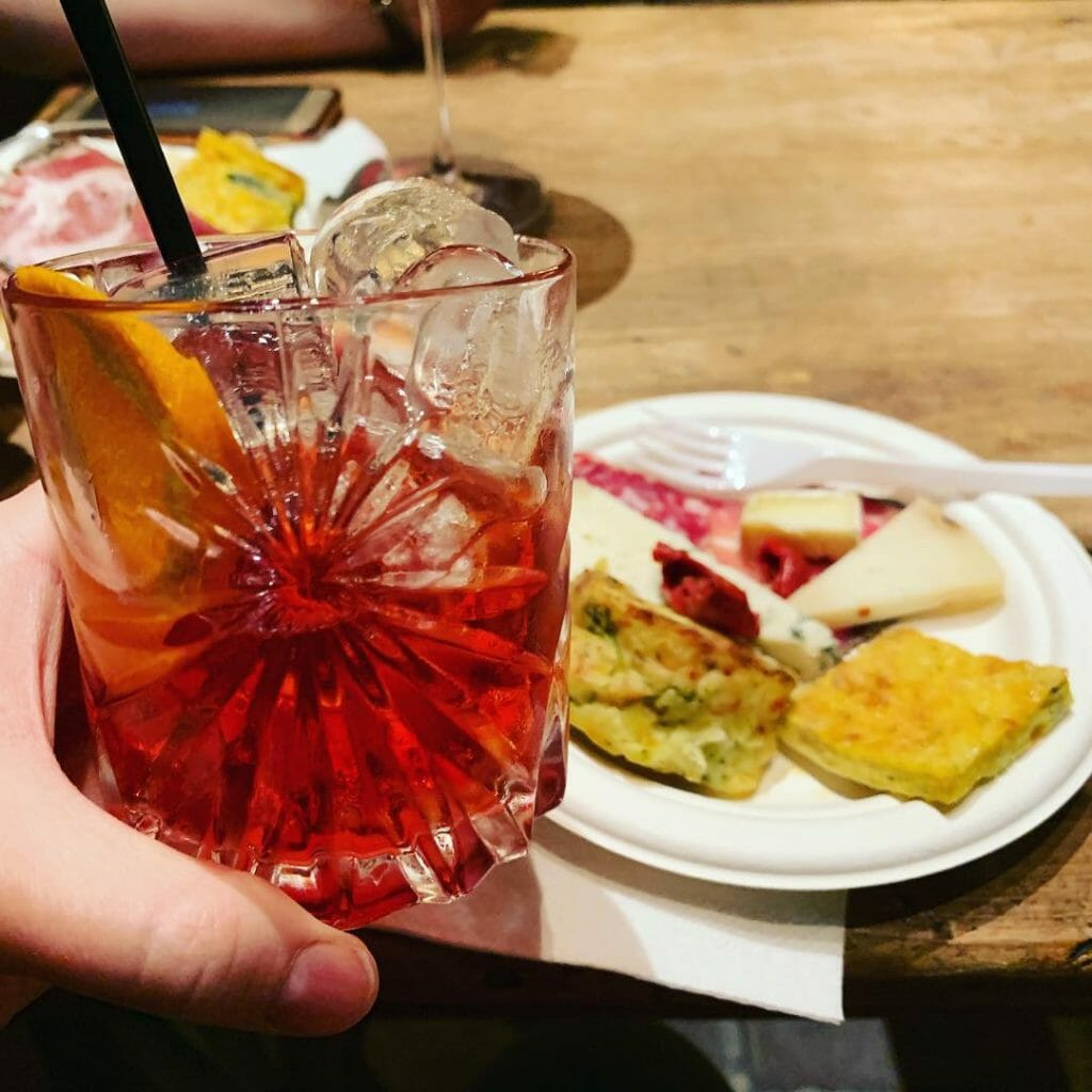 Hand holding negroni glass in front of a plate of snacks (cheese & ham etc)